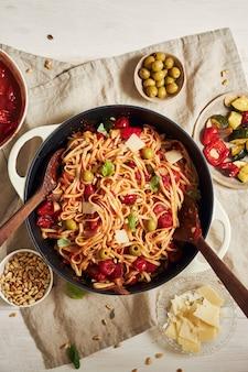 Primo piano di pasta con verdure e ingredienti su un tavolo bianco