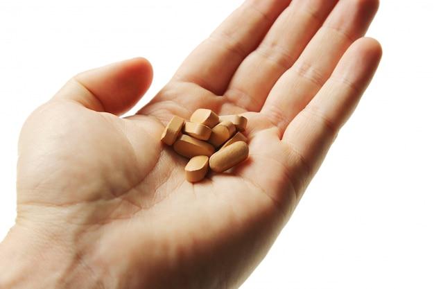 Colpo del primo piano di una persona che tiene un mazzo di pillole su bianco