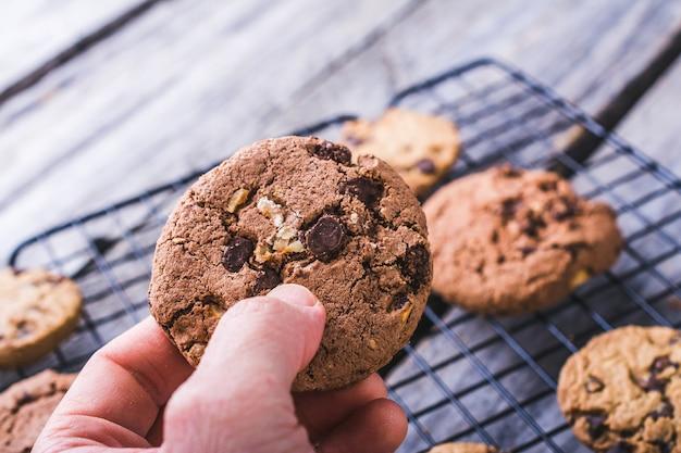 Colpo del primo piano di una persona che tiene un biscotto con gocce di cioccolato su uno sfondo sfocato