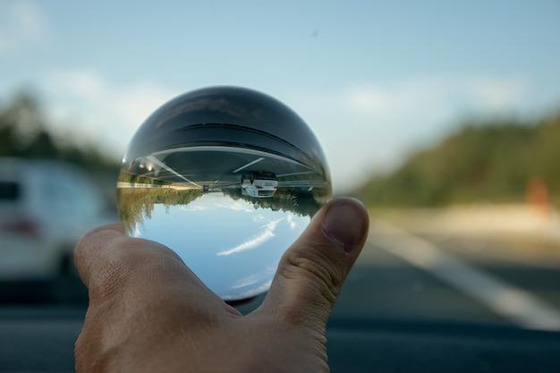 Colpo del primo piano di una persona che tiene una sfera di cristallo con il riflesso degli alberi