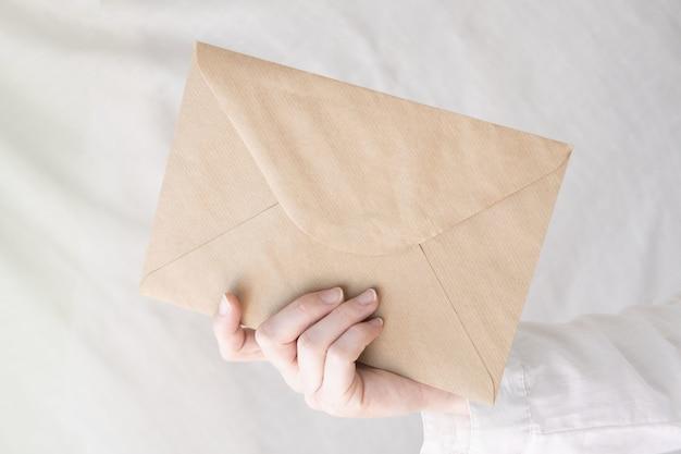 Primo piano della mano di una persona che tiene una busta