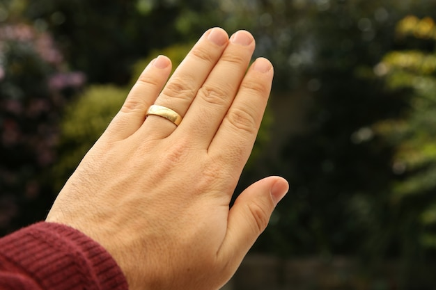 Closeup shot of a person's hand wearing a golden wedding ring with a blurred natural