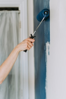 Colpo del primo piano di una persona che usando i rulli di pittura con il blu di colore