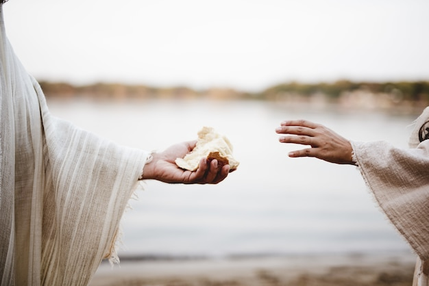 Closeup shot of a person wearing a biblical robe giving bread to another person
