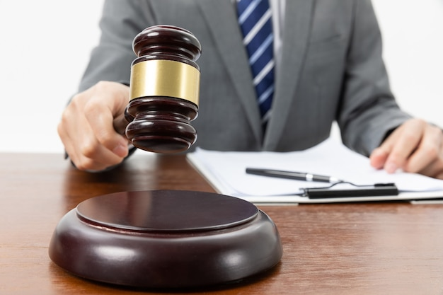 Closeup shot of a person with a gavel in hand and papers on the table