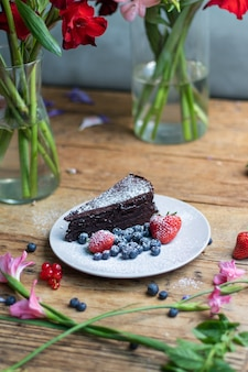 Closeup shot of a piece of brownie cake with blueberries and strawberries