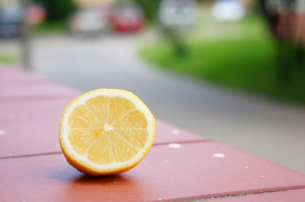 Closeup shot of a piece of cut lemon on a wooden surface