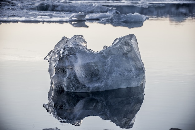Closeup shot of a piece of ice floating in the ocean and reflected in it in jokulsarlon, iceland