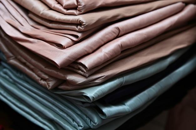 Colpo del primo piano delle pile di stoffa colorata e tessuti in un negozio