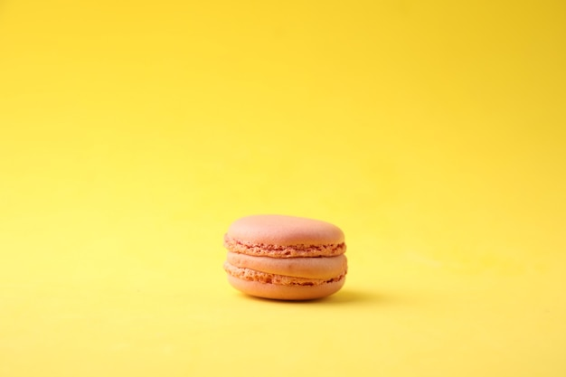 Closeup shot of a pink macaroon on a yellow background