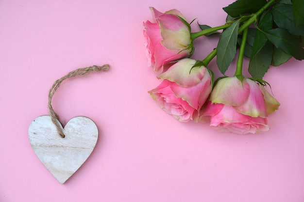 Closeup shot of pink rose flowers with a heart wooden tag with space for text on a pink surface