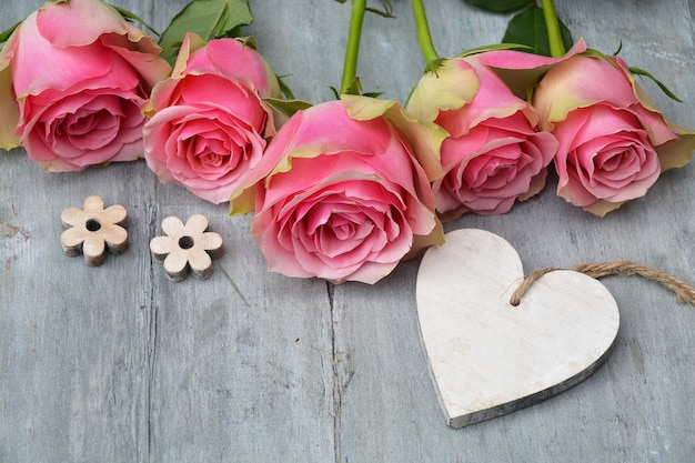 Colpo del primo piano dei fiori di rosa rosa con un'etichetta di legno del cuore con spazio per testo su una superficie di legno
