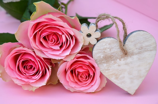 Closeup shot of pink rose flowers with a heart wooden tag with space for text