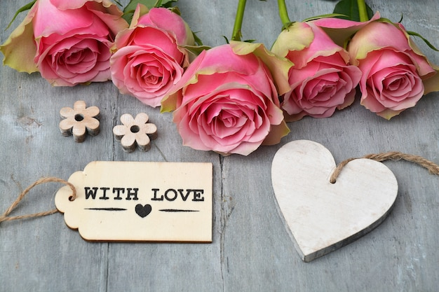 Closeup shot of pink roses next to an empty heart wooden tag and a with love tag on a wooden surface