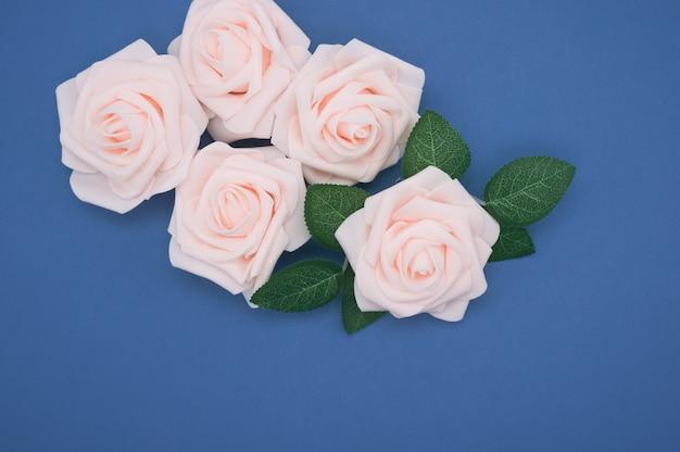 Closeup colpo di rose rosa isolato su uno sfondo blu con spazio di copia