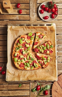 Primo piano di una pizza con verdure su un tavolo di legno