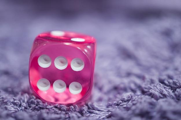 Colpo del primo piano di un dado di plastica rosa con sei punti su un tessuto morbido