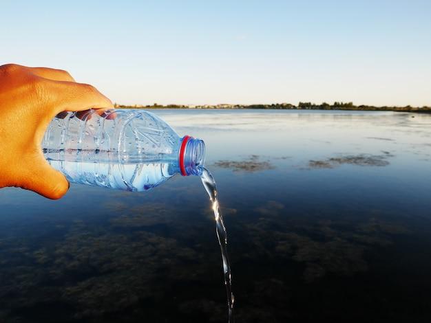 Primo piano di una bottiglia d'acqua di plastica in una mano umana perfetta per il concetto di spreco d'acqua