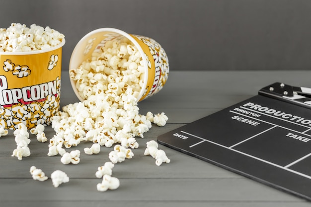 Closeup shot of popcorn buckets next to a clapperboard on a gray background