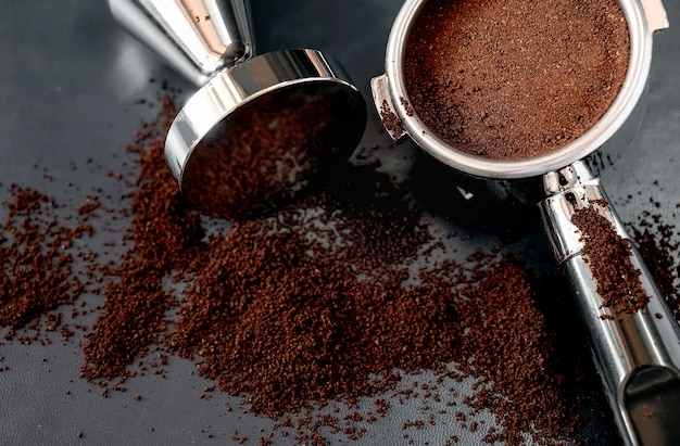 Closeup shot of portafilter with coffee and tamper on black leather background
