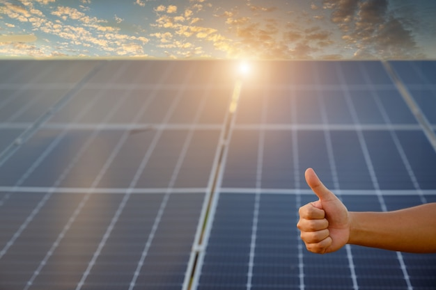 Closeup shot poses positive gesture on solar panel photovoltaic on the roof of the house and with a thumbs up or like money saving and clean energy ideas.