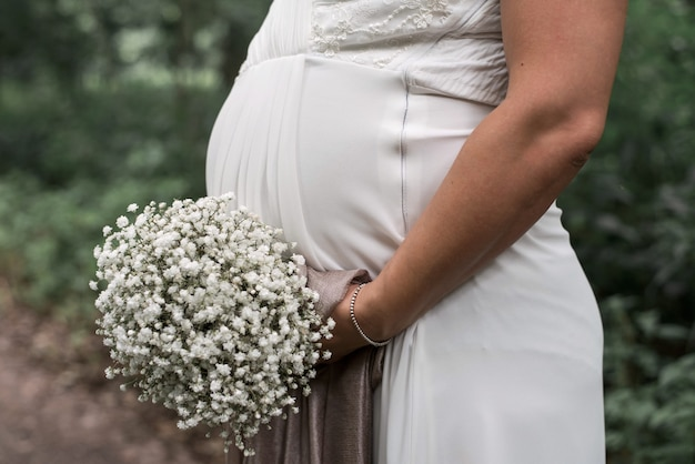 Closeup shot of a pregnant bride holding a white bouquet on her wedding day