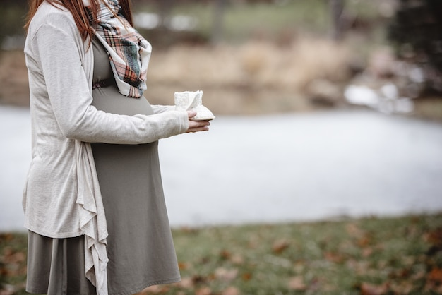 Closeup shot of a pregnant woman holding baby shoes