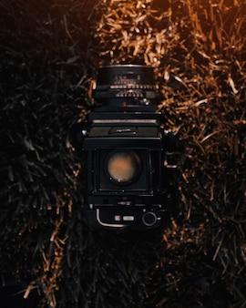 Colpo del primo piano di una macchina fotografica professionale della terra su erba