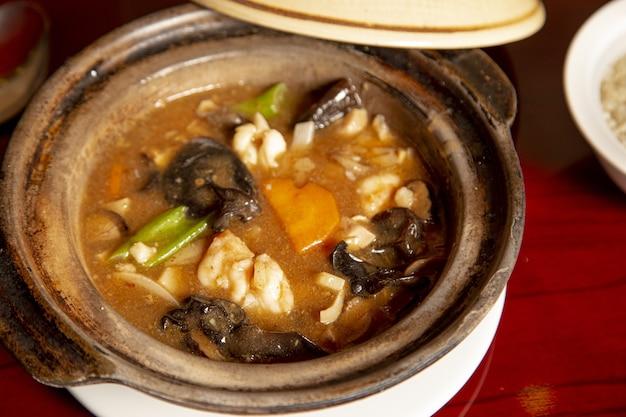 Primo piano della casseruola di riso soffiato con rana pescatrice e frutti di mare su una superficie di legno