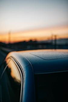 Primo piano di gocce di pioggia sulla parte superiore di un'auto con il cielo al tramonto che si riflette nelle finestre