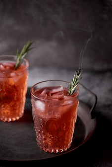 Closeup shot of red alcohol drinks with rosemary leaves on a tray