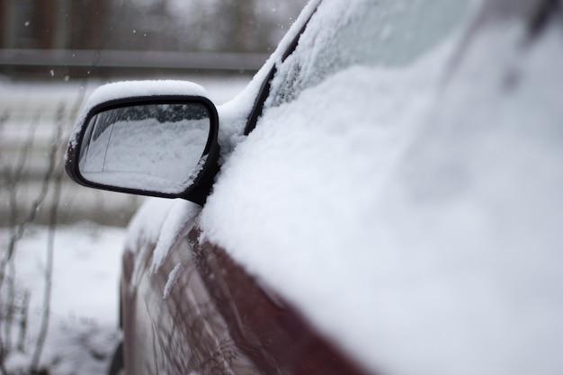 Primo piano di un'auto rossa ricoperta di neve