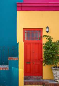 Closeup shot of the red door of a yellow building and a plant next to it