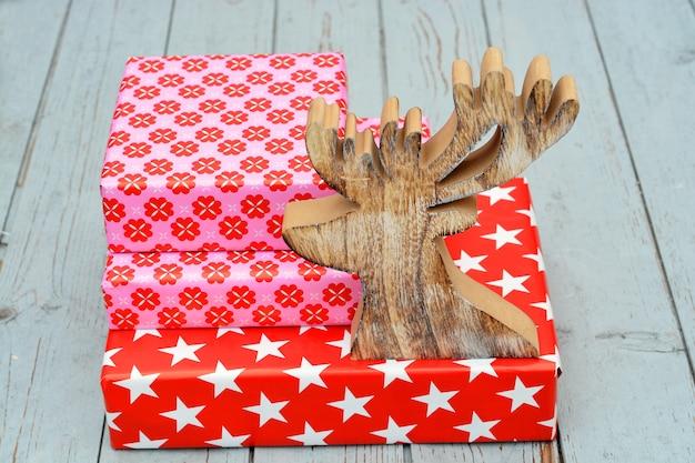 Colpo del primo piano di scatole regalo rosse impilate una sopra l'altra e una figura di renna in legno