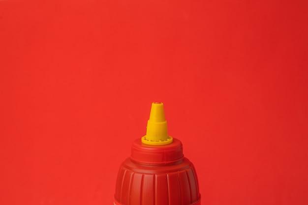 Colpo del primo piano della bottiglia di ketchup rosso su una parete rossa