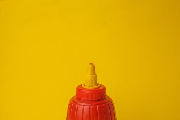 Colpo del primo piano di una bottiglia di ketchup rossa su una parete gialla
