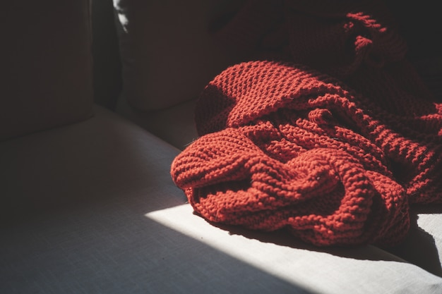 Closeup shot of a red textile on a wooden surface illuminated with the sunlight
