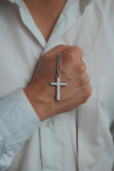 Closeup shot of a religious male holding a silver necklace with a cross pendant