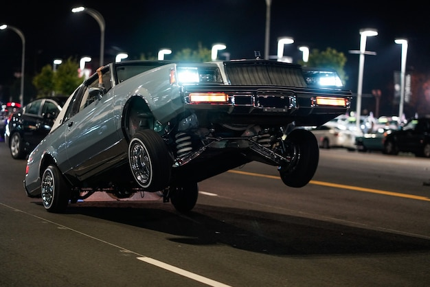 Closeup shot of a retro car with only the back wheels on the ground in a street at night