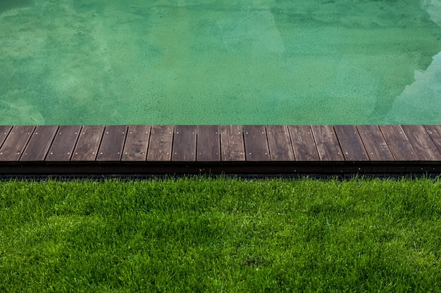 Closeup shot of riverbank with wooden path and green lawn