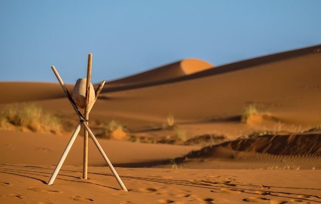 Closeup shot of a rock on a stick tripod with blurred sand dunes