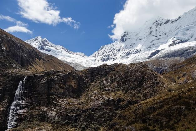 Colpo del primo piano delle vette rocciose con parti nella neve
