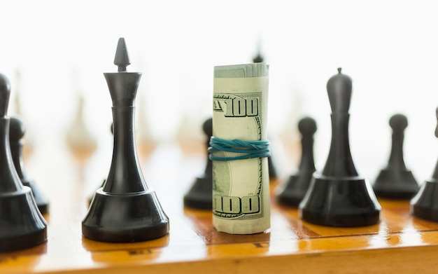 Closeup shot of rolled dollars on place o black chess piece