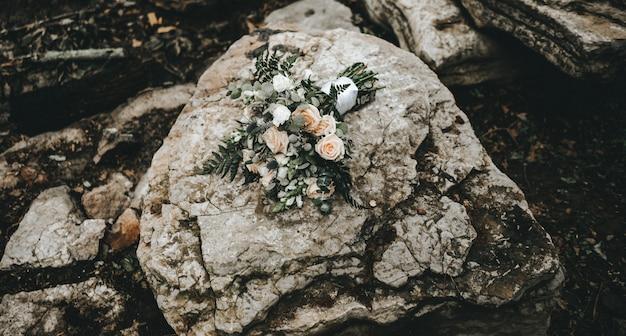 Colpo del primo piano di un mazzo di rose su una roccia