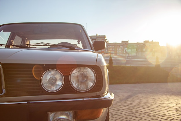 Closeup shot of the round headlight of a white vintage classic car during sunset