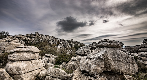 Closeup shot of several grey rocks on top of each other under a cloudy sky