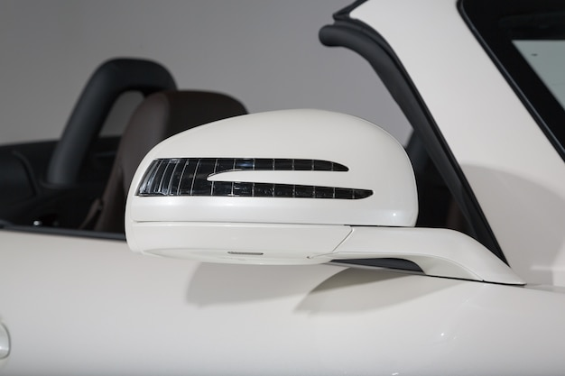 Closeup shot of the side mirror of a modern white cabriolet car