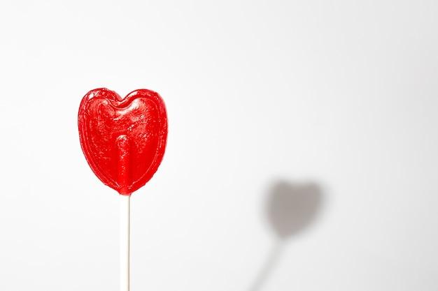 Colpo del primo piano di un singolo lecca-lecca a forma di cuore su una priorità bassa bianca
