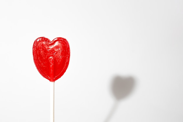 Closeup shot of a single heart-shaped lollipop on a white background