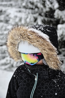 Closeup shot of a skier wearing fur hooded jacket and goggles at alpe d huez ski resort, france